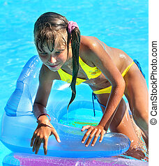 Child on inflatable beach mattress. - Little girl on...