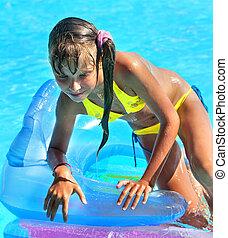 Child on inflatable beach mattress. - Little girl on...