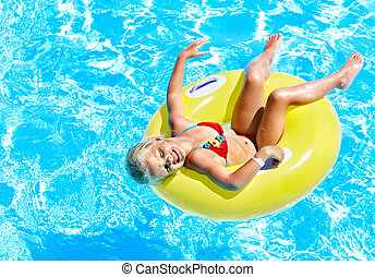 Child on inflatable in swimming pool.