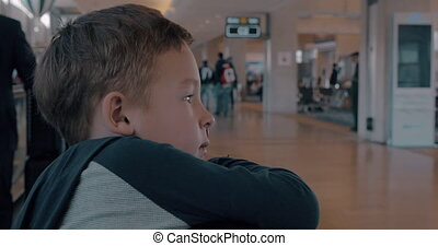 Child on moving walkway at the airport - Boy leaning on...