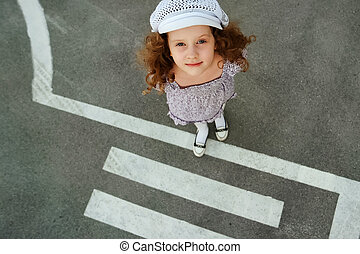 Child on road with pedestrian crossing.