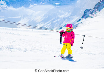 Child on ski lift in snow sport school in winter mountains -...
