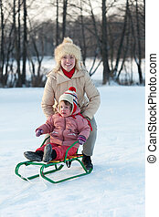 child on sled with mother in winter