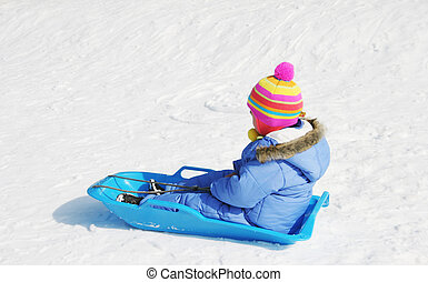 Youngster wearing colorful ski clothing rides a sled