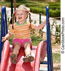 Child   on slide in playground.Outdoor park.