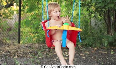 Child on swing in garden