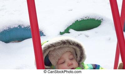 Child on swing in winter