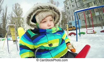 Child on swing in winter - Baby boy on swing ride in winter