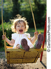 Child on swing - Laughing child on swing in summer park