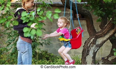 Child on swing with mother