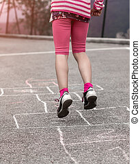 Child on the hopscotch - Litlle girl playing on the...