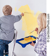Child on the ladder painting the wall