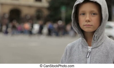 Child on the road against a background of blurry cars - A...