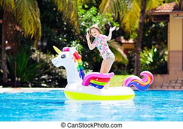 Child on unicorn float in swimming pool. Kids swim