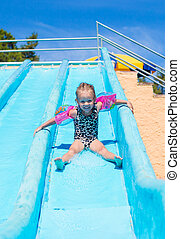Child on water slide at aquapark during summer holiday
