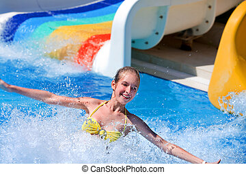Child on water slide at aquapark. - Happt teen girl on water...
