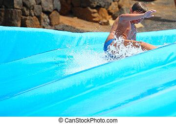 Child on water slide at aquapark