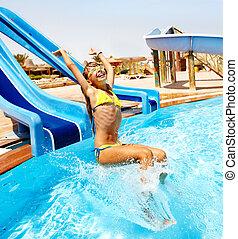 Child on water slide at aquapark.
