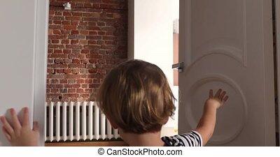 Child opens the door handle - Kid opens the door to room and...