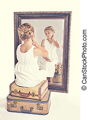 Child or young girl staring at herself in a mirror, sitting...