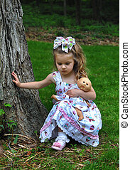 Child Outdoors With Her Doll