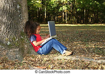Child Outside with Laptop - Seven year old child outside...