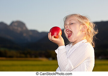 Child outside with red apple - Child is holding a red apple ...