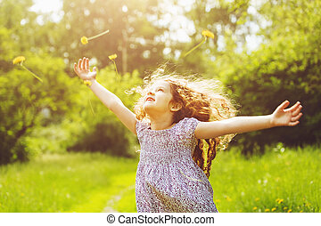Child outstretched arms enjoying flying yellow dandelion in...