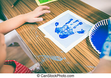 Child paint her palm on art class. Education and learning concept. Vintage tone.