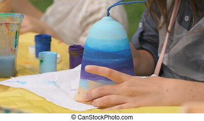 Child painting brushes on the clay figure outdoors - Unknown...