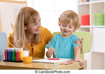 Child painting in preschool. Teacher help by little boy.