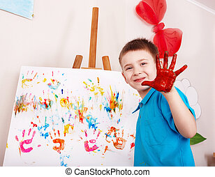 Child painting on easel by hands.  Preschool.