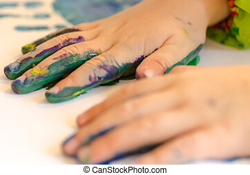 Child painting with hands