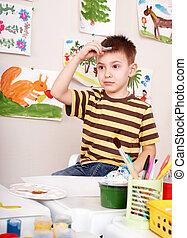 Child paints in art class.