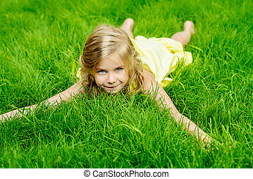 child paradise - Cute little girl lies on a green lawn in...