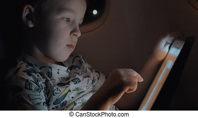 Child passing time with pad during night flight