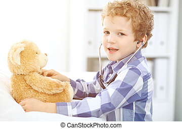 Child  patient afrer health exam playing as a doctor with stethoscope and teddy bear