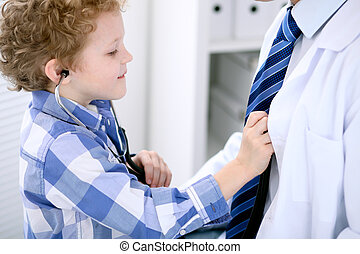 Child patient examining his doctor by stethoscope