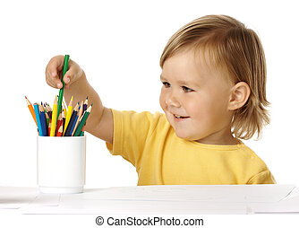 Child picking green crayon from the cup
