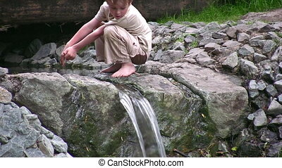 child play on small waterfall