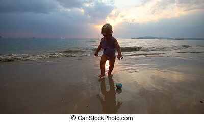 child play on the beach at sunset