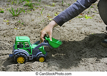 Child play with a plastic excavator.