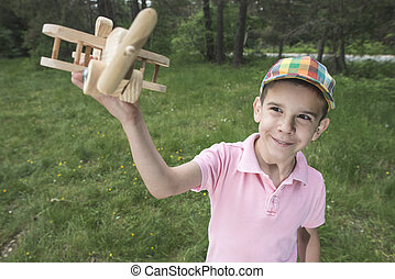 Child play with a wooden plane in the mountain