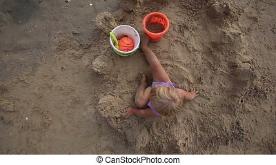 child play with ball and bucket on the sand