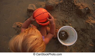 child play with ball and bucket sit on the sand