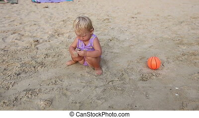 child play with ball on the sand
