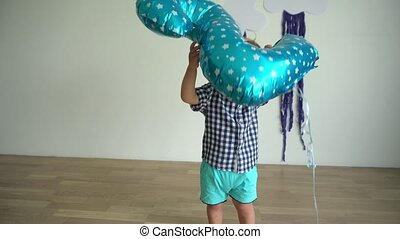 Child play with balloon. Little boy celebrating second...