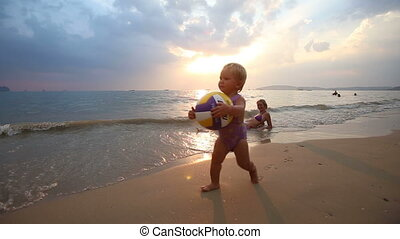 child play with mom on the beach at sunset
