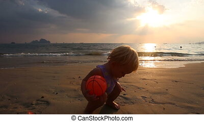 child play with pebble and ball at sunset