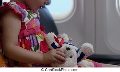 Child play with toy white sitiing in cabin of plane or aircraft cabin. Adorable little girl traveling by an airplane. Child sitting by aircraft window and playing with toy plane.